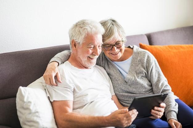 Paar senioren glimlachen en kijken naar dezelfde tablet geknuffeld op de bank - binnen, thuis concept - blanke volwassen en gepensioneerde man en vrouw die technologie gebruiken