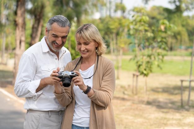 Paar senioren met pensioen die fotografie beoefenen en samen naar camerabeelden in het park kijken