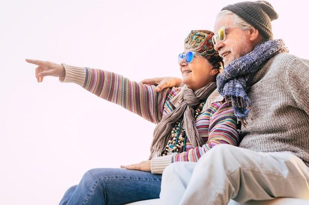 Paar senioren omhelsd samen met winterkleren glimlachend en iets laten zien - gelukkige volwassen mensen samen in vrijetijdsbesteding in de buitenlucht