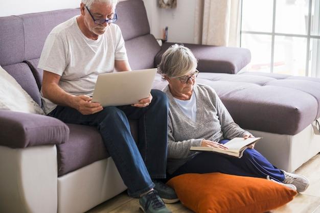 Paar senioren ontspannen en genieten thuis op de bank - volwassen en gepensioneerde vrouw leest een boek in stilte op de grond en man aan het werk met zijn laptop of computer pc