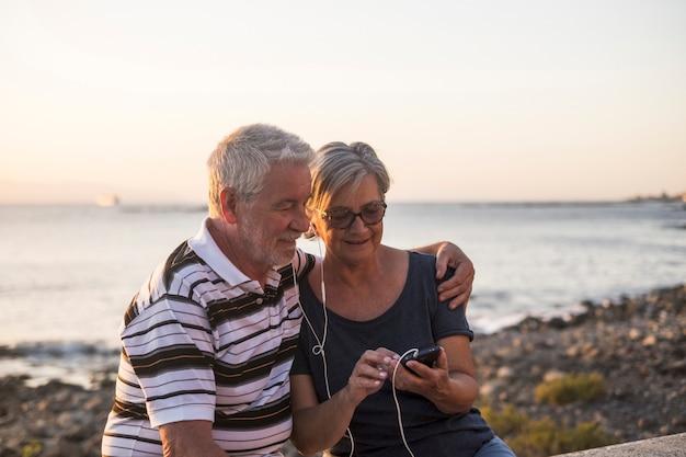 Paar senioren op het strand luisteren samen naar muziek met dezelfde telefoon en hetzelfde nummer - vrouw met bril en gepensioneerde man genieten alleen - zee en rotsen op de achtergrond - zonsondergangmoment
