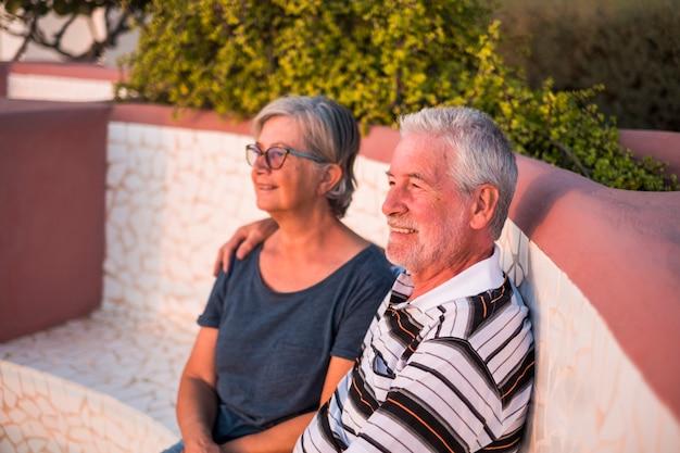 Paar senioren op het strand met veel liefde bij de zonsondergang - samen met pensioen - vrouw met bril en man met zee achtergrond