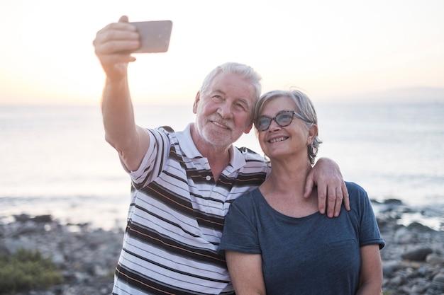 Paar senioren op het strand samen een foto maken - vrouw met bril en gepensioneerde man - selfie op het strand - veel plezier en genieten - kaukasisch