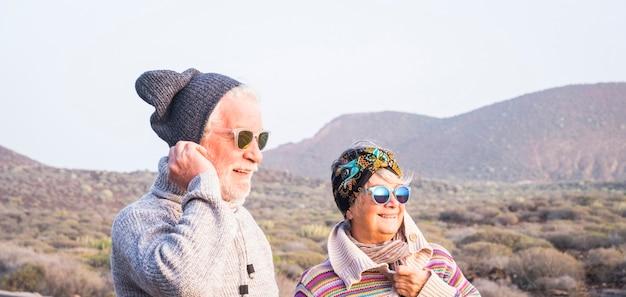 Paar senioren samen kijken naar de horizon met de berg - reizigers bij winter lifestyle concept - getrouwde volwassen mensen die samen plezier hebben in vrijetijdsbesteding buitenshuis