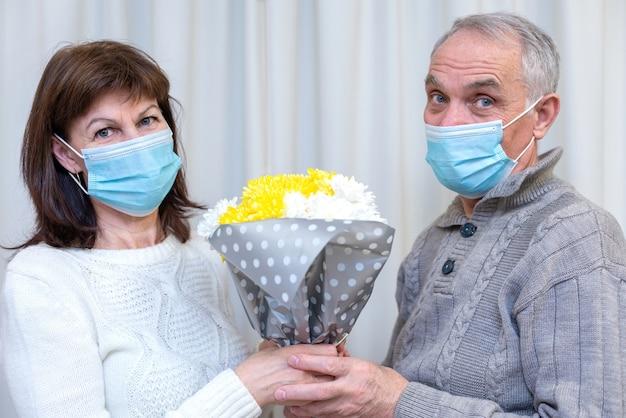 Paar senioren vieren valentijnsdag in masker. man geeft vrouw een favoriet boeket bloemen