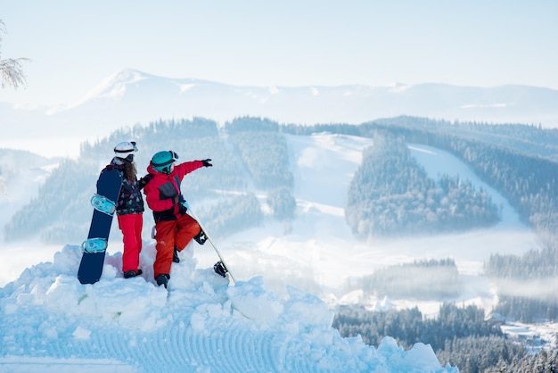 Paar snowboarders bovenop een berg