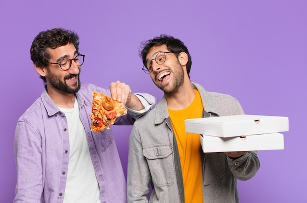 Paar spaanse vrienden blije uitdrukking en houden pizza's mee