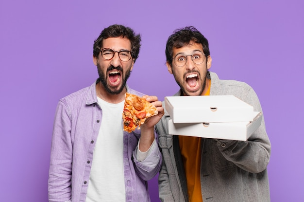 Paar spaanse vrienden boze uitdrukking en houden afhaalpizza's vast