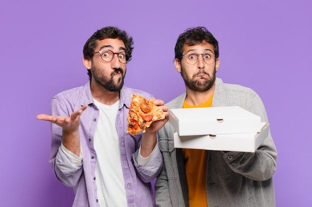 Paar spaanse vrienden die twijfelen of een onzekere uitdrukking hebben en afhaalpizza's vasthouden?
