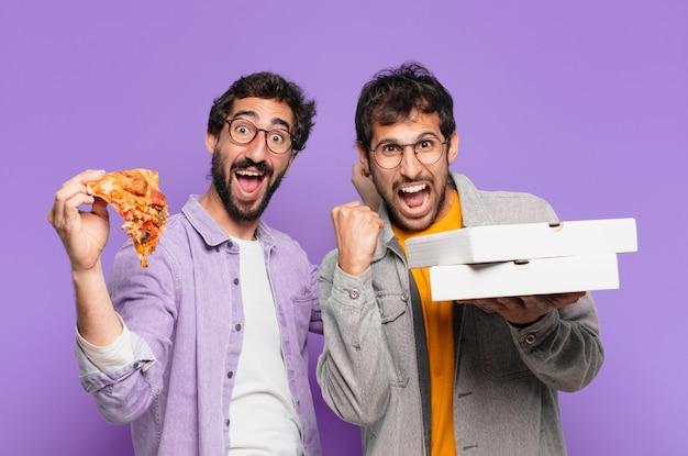 Paar spaanse vrienden verraste uitdrukking en hield afhaalpizza's vast?