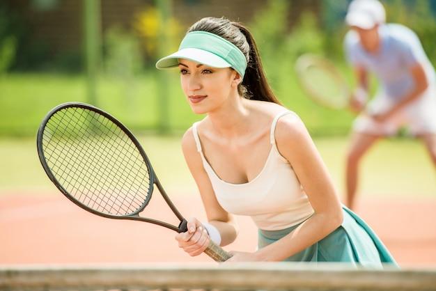 Paar spelen dubbelspel op de tennisbaan.