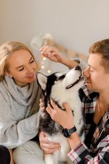 Paar spelen met hond in slaapkamer