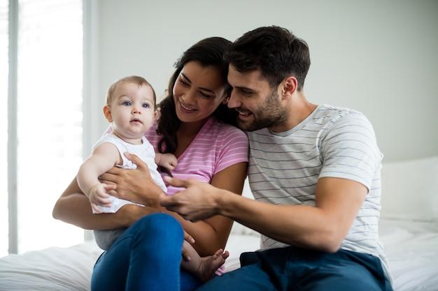 Paar spelen met hun babymeisje op bed thuis