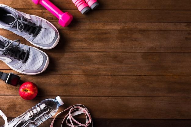 Paar sportschoenen, appel, springtouw en halter op houten tafel