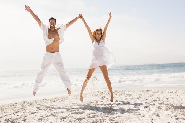 Paar springen op het strand