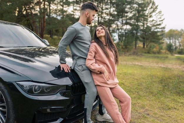 Paar staat in de buurt van auto