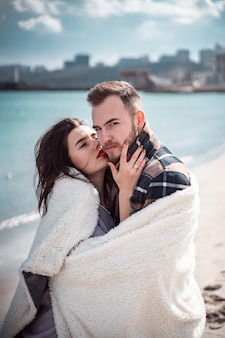 Paar staat op het strand en poseren