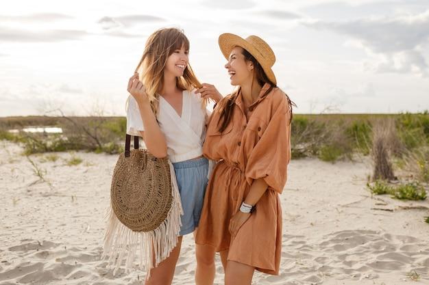 Paar stijlvolle meisjes wandelen en genieten van geweldige kust nieuwe oceaan. rieten tas, modieuze outfit.