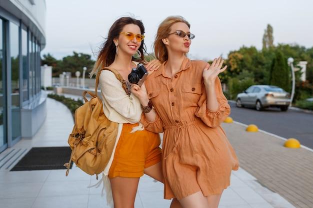 Paar stijlvolle vrouwen na het verlaten van reis stellen openlucht dichtbij luchthaven