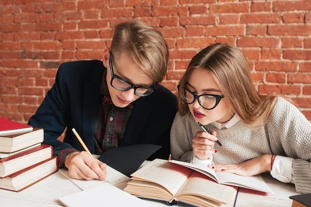 Paar studenten die zorgvuldig leerboek lezen