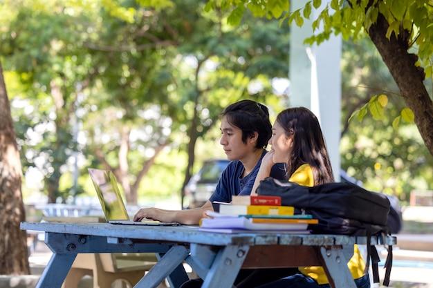 Paar studenten zitten en gebruiken laptop in openluchtuniversiteit die wat online onderzoek doet