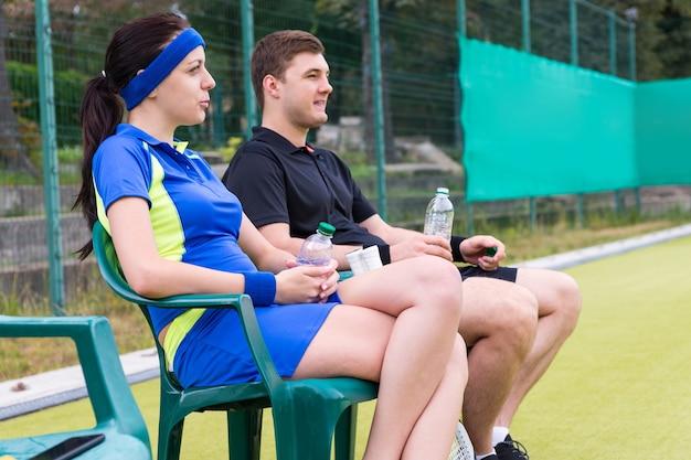 Paar tennissers die een sportkleding dragen die een rust met een fles water op de stoelen bij de tennisbaan hebben