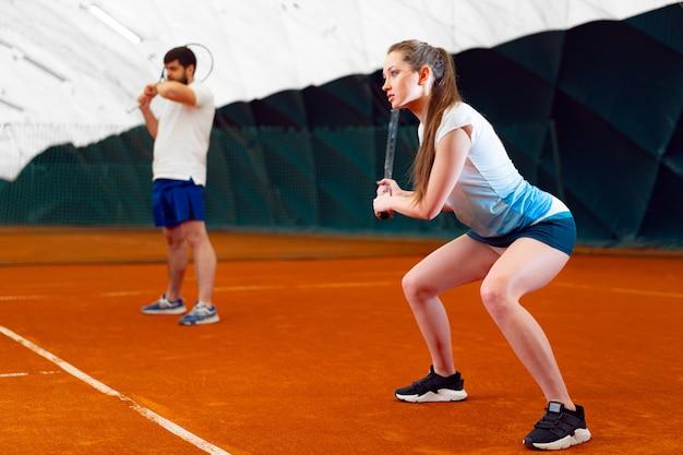 Paar tennissers, man en vrouw te wachten op service op indoor court