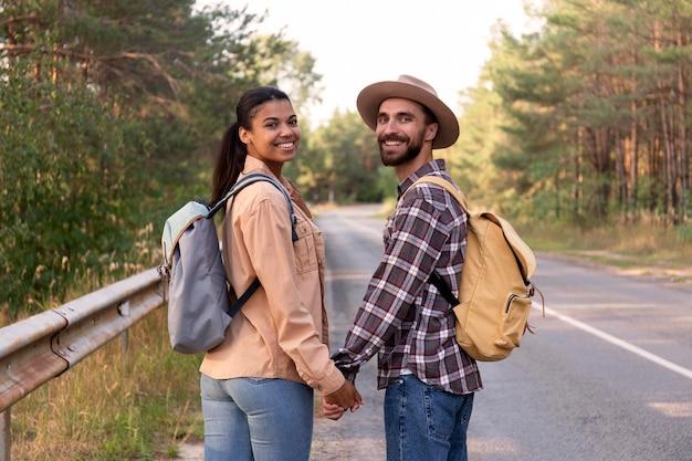 Paar terugkijkend terwijl hand in hand