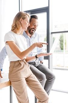 Paar tevreden collega's die aan laptop werken