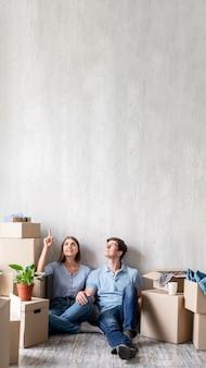 Paar thuis inpakken om te verhuizen en naar boven te wijzen