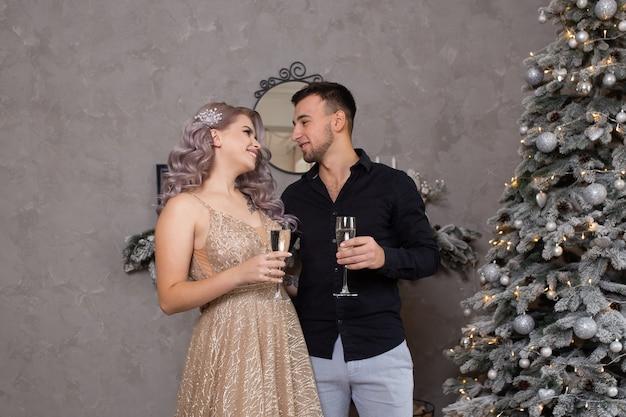 Paar thuis met kerstmis in de buurt van prachtig versierde kerstboom