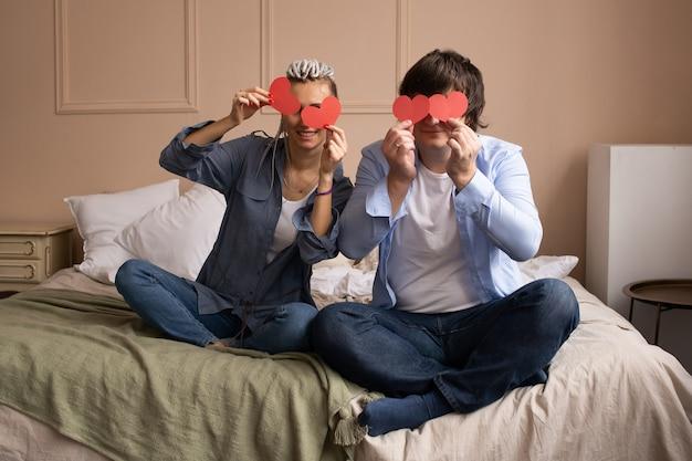 Paar thuis spelen met elkaar met rood hart valentines in handen.