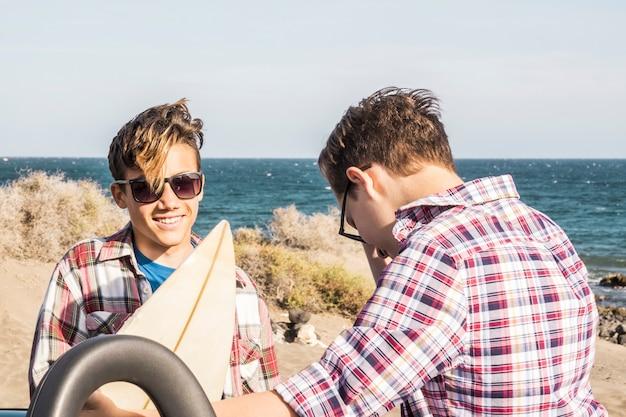 Paar tieners glimlachen en hebben plezier samen op het strand, surfer jongen en surfen - surfen - 20s met bril en zonnebril buiten wachten om te gaan surfen met zee op de achtergrond