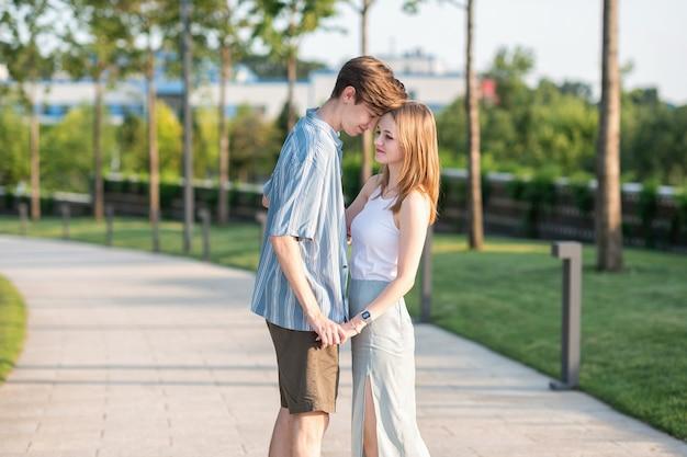 Paar tieners hand in hand en knuffelen in het park de eerste liefde