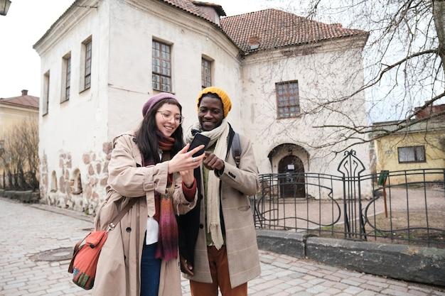 Paar toeristen die foto's maken op mobiele telefoon tijdens het wandelen in de stad