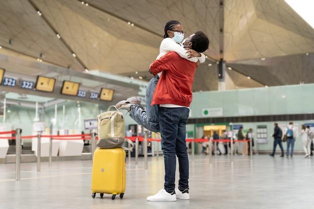 Paar toeristen in maskers knuffelen in luchthaven