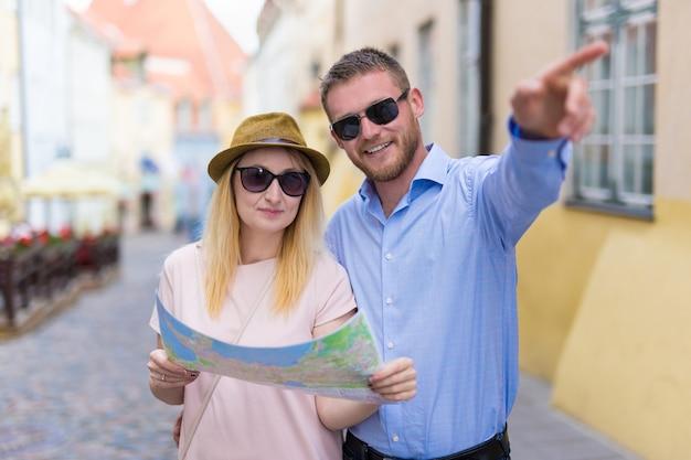 Paar toeristen wandelen in de stad met papieren kaart