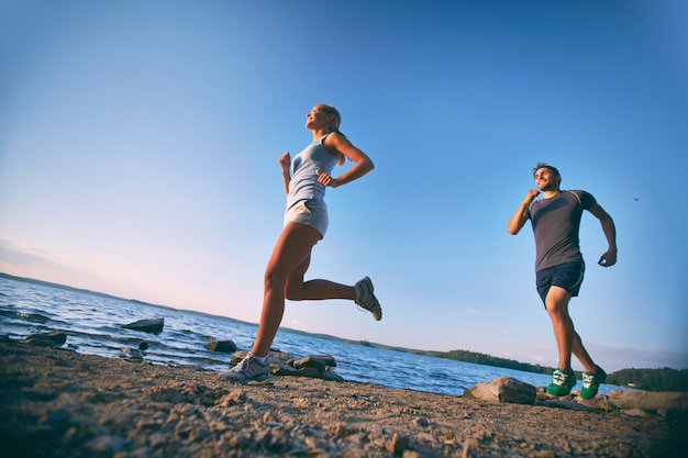 Paar training in de ochtend op het strand