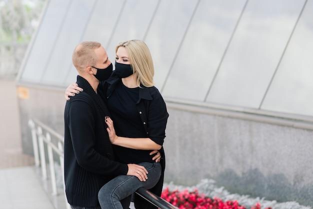 Paar trendy modieuze beschermende maskers, spijkerjassen, wandelen in lege straat van europese stad tijdens quarantaine van coronavirus-uitbraak.