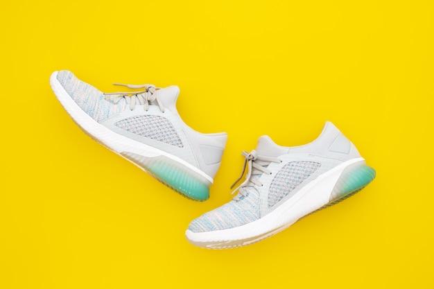 Paar trendy sportschoenen op gele achtergrond.