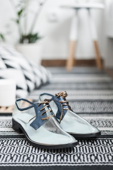 Paar trendy transparante schoenen op geweven kleed