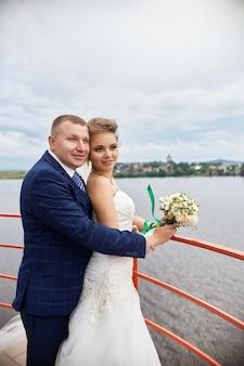 Paar trouwen omhelzen en kussen naast huizen in de buurt van water