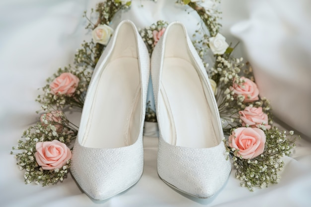 Paar trouwschoenen met roze rozen en gypsophilas
