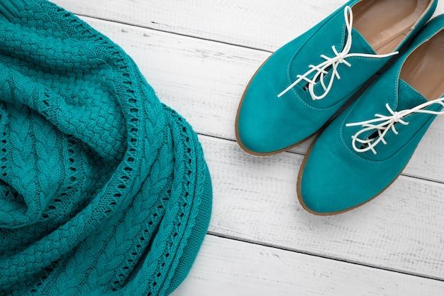 Paar turquoise suède lage laarzen en gebreide aquakleurige trui.