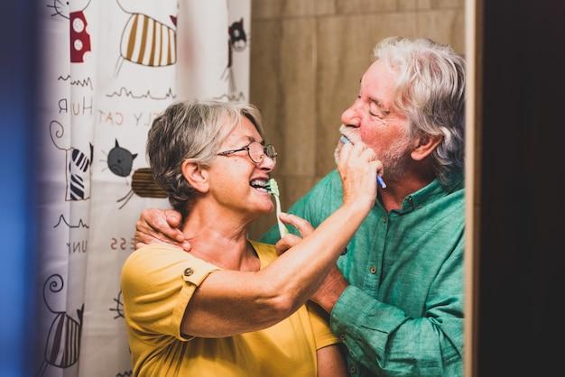 Paar twee gelukkige en lachende senioren die hun tanden van elkaar poetsen thuis in de badkamer - zelfzorg en voor zichzelf zorgen