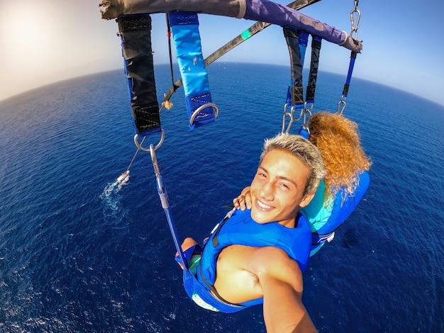 Paar twee gelukkige mensen die genieten van de zomer en vakanties die extreme activiteiten op zee doen