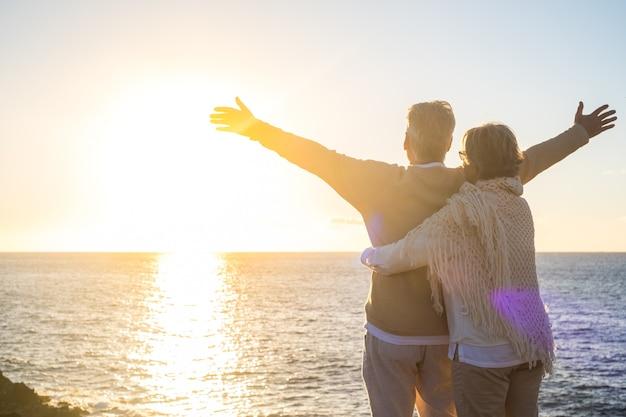 Paar twee gelukkige senior advertentie volwassen oude mensen op het strand kijken naar de zee en de zon met geopende armen vrijheid voelen. vrijheidsconcept en levensstijl