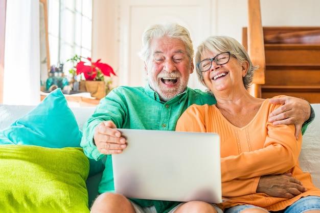Paar twee gelukkige volwassen en oude mensen of senioren thuis zittend op de bank genieten en plezier hebben samen op zoek en met behulp van een laptop of computer pc
