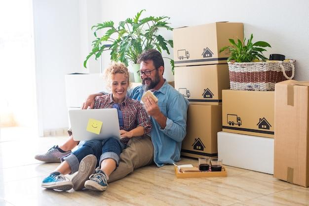 Paar twee gelukkige volwassenen en mensen die op de grond zitten met hun laptop samen en een snack eten na het afsluiten van een hypotheek