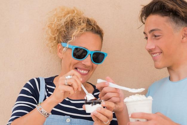Paar twee mensen, ze zijn zoon en moeder die milkshake en ijs eten samen glimlachend en plezier